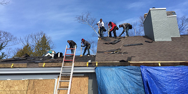 workers repairing a roof of a house